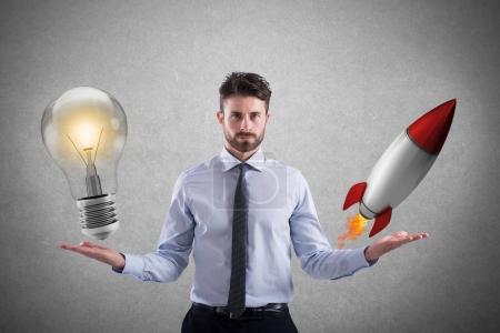 Businessman compares a lightbulb to a rocket.