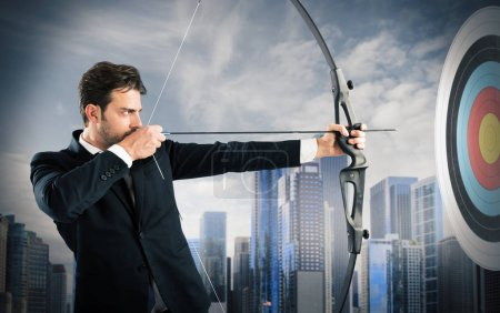 Photo for Businessman with bow and arrow aiming a target - Royalty Free Image