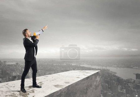 Photo pour Homme d'affaires faisant une annonce au mégaphone par-dessus un toit - image libre de droit