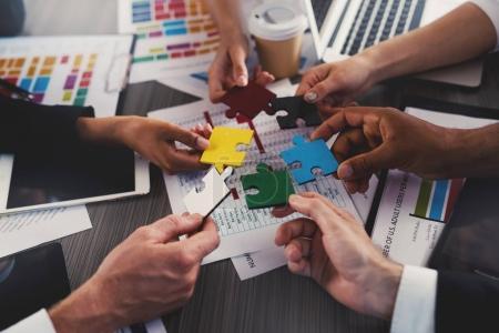 Photo pour Hommes d'affaires travaillent ensemble pour construire un puzzle coloré. Concept de travail d'équipe, partenariat, intégration et mise en service. - image libre de droit