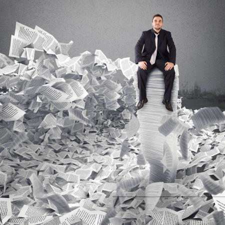 Businessman with paper sheets anywhere. Buried by bureaucracy concept.