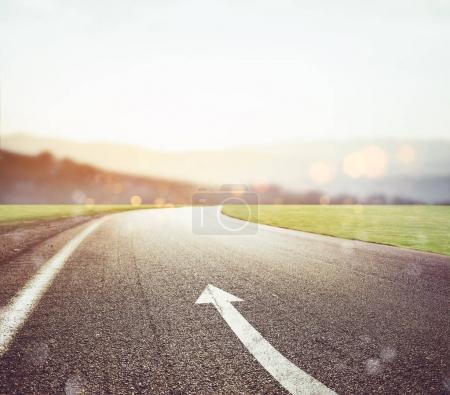 Photo pour Route avec panneau fléché sur l'asphalte avec soleil devant. Concept - image libre de droit