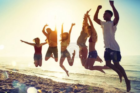 Photo for Happy smiling friends jumping over the sea of the beach - Royalty Free Image