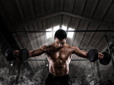 Photo for Athletic muscular man training biceps with dumbbells at the gym - Royalty Free Image