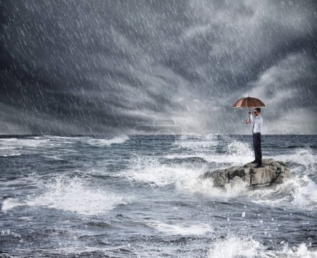 Businessman with umbrella during storm