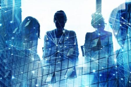 Photo for Silhouette of businesspeople  in a modern office with skyscraper effect. concept of partnership and teamwork - Royalty Free Image