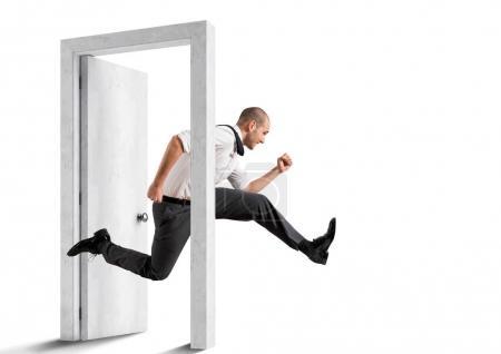 Businessman crossing  a door.