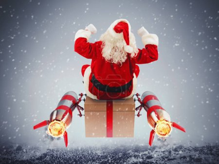 Photo for Santa Claus with gift box flies with rockets on space - Royalty Free Image