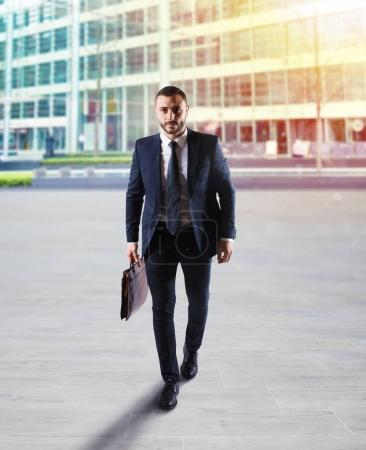 Businessman walking on the street with skyscraper background.