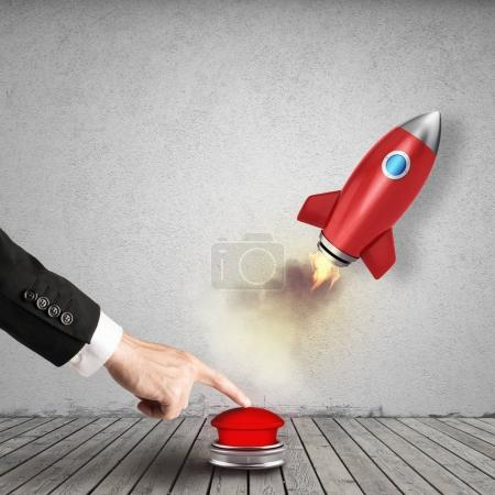 Businessman launching  rocket pushing a red button. 3D Rendering