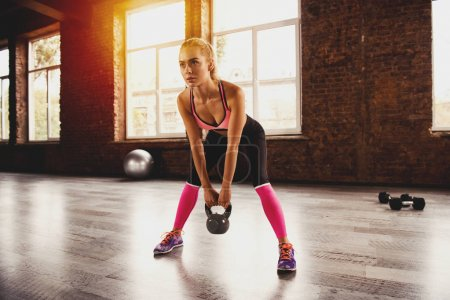 Determined blonde girl working out at the gym with a kettlebell. crossfit exercise