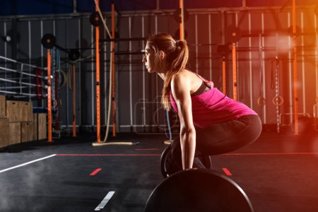 Determined athletic girl working  out at the gym with a barbell