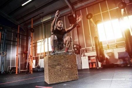Homme, faire des exercices de saut en boîte