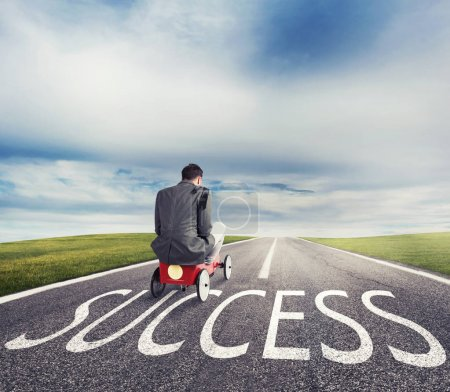 Man runs with a toy car on success way. Concept of successful businessman and company startup