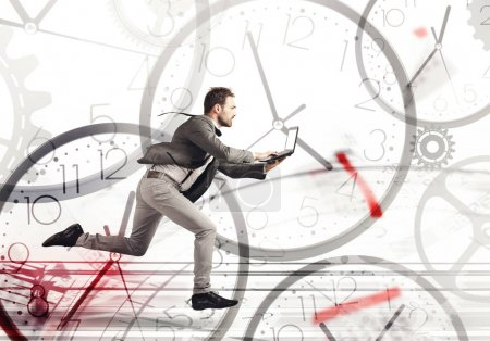 Photo for Business man runs fast with a laptop on a background of clocks - Royalty Free Image