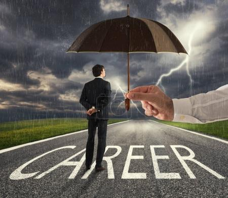 Businessman ready to start a difficult career way with a big help of an umbrella. concept of support and assistance