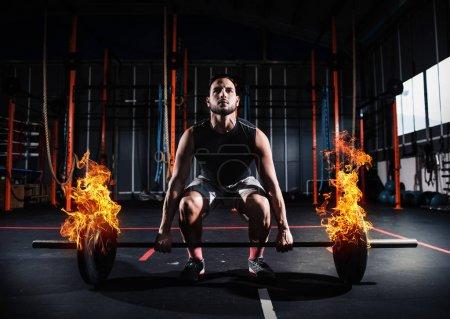 L'homme athlétique revient à la salle de gym avec une barre de feu