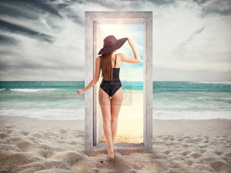 Woman crosses a door on the beach leading to the summer season.