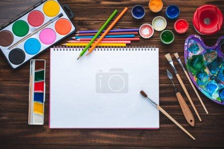 Ensemble de peintures, crayons, outils de peinture et blanc livre blanc feuille de carnet de croquis sur fond en bois vintage. Vue de dessus