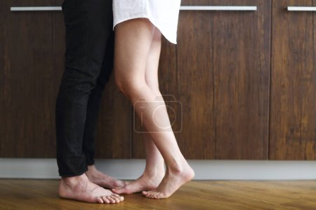 Photo pour Jeune couple baisers et câlins à la cuisine le matin - image libre de droit