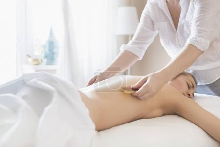 Young woman take back treatment at health spa
