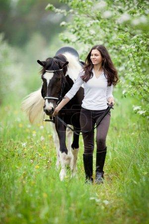 Photo pour Jeune femme et cheval pinto dans jardin d'apple. Cheval et belle dame marche en plein air. Cavalier de cheval. - image libre de droit