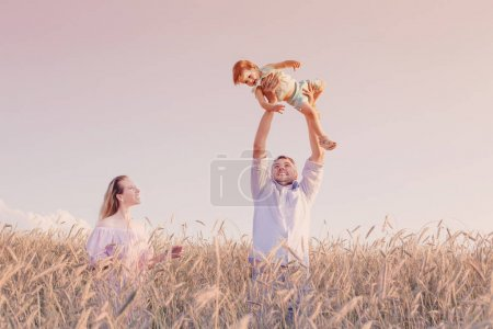 happy family in cereal field at sunset