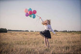 teenager with  balloons in summer field
