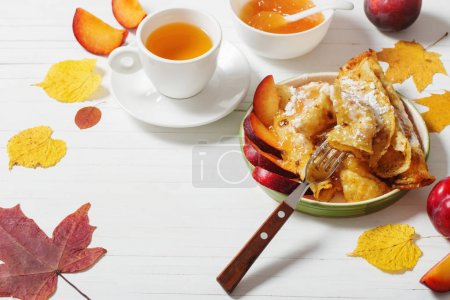 pancakes with tea  and plums on white wooden table