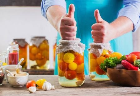 men with vegetables in jars