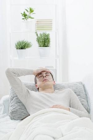 a man with a headache on the sofa