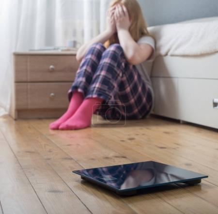 Photo for Sad teenager girl with scales on floor - Royalty Free Image
