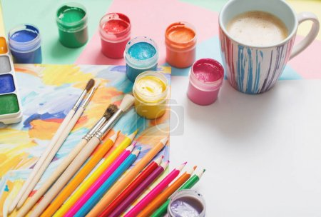 cup of coffee and paints, pencils on white background