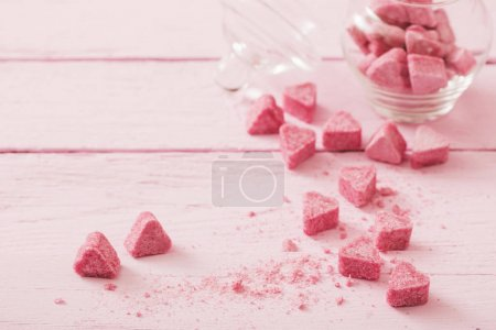 Granulated pink sugar  in the shape of heart on a wooden backgro