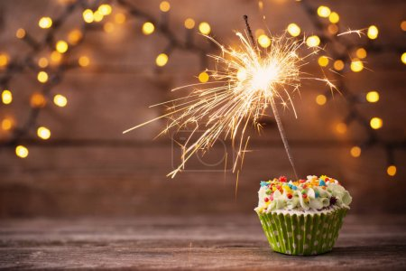 Photo for Cupcake with sparkler on old wooden background - Royalty Free Image