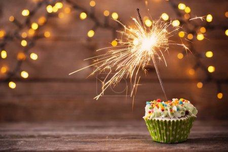 Foto de Cupcake con luces de Bengala sobre fondo de madera vieja - Imagen libre de derechos