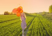 happy girl with balloons on field