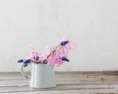 spring flowers in blue jug on grunge background
