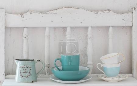 Photo for Dinnerware on white wooden shelf - Royalty Free Image