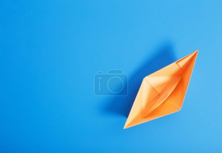 Photo for Paper boat on blue paper background - Royalty Free Image
