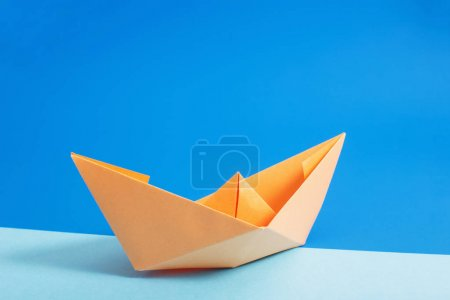 paper boat on blue paper background
