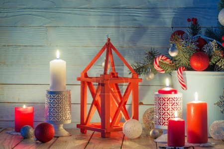 Christmas decorations with burning candles on blue...