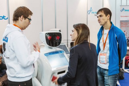 Visitors inspect the exposition of robots and new technologies