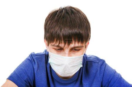 Photo pour Triste jeune homme dans le masque de la grippe isolé sur le fond blanc - image libre de droit