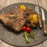 On wooden table background juicy beef steak medium...