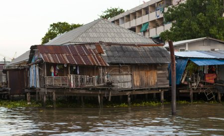 The old shacks, hovel houses stand on stilts in the water on the waterfront. Houses of poor people. Thailand Bangkok