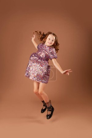 Photo pour Jolie fille en robe de paillettes sauté - image libre de droit