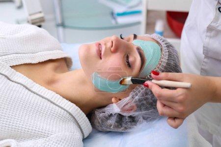 Photo pour Jeune belle femme recevant un masque facial en argile dans un salon de beauté spa - image libre de droit