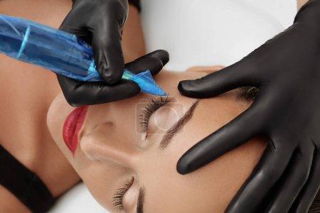 Photo pour Cosmetologue appliquant un maquillage permanent sur les sourcils tatouage des sourcils - image libre de droit