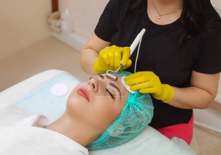 Photo for The cosmetologist makes the apparatus a procedure of Microcurrent therapy of a beautiful, young woman in a beauty salon. Cosmetology and professional skin care. - Royalty Free Image